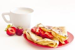Süße Pfannkuchen mit Erdbeere und Cup Milch lizenzfreie stockbilder
