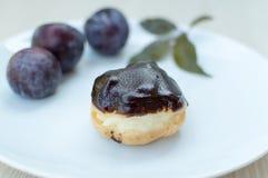 Süße profiteroles mit Sahne und Schokoladenglasur und -pflaumen auf a lizenzfreies stockfoto