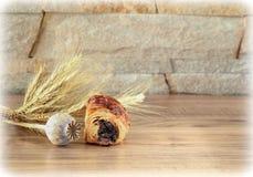 Süße Rolle mit Mohnblume liegt auf einem Holztisch mit einem Mohnblumenkopf und -ährchen Stockfoto