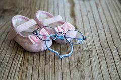 Süße rosa Babyschuhe und Gläser auf dem hölzernen Hintergrund Lizenzfreies Stockbild