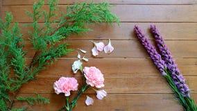 Süße rosa und purpurrote Blumen auf hölzernem Tabellenhintergrund Lizenzfreie Stockbilder