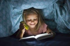Süße schöne und recht kleine blonde bettabdeckungs-Lesebuch des Mädchens 6 bis 8 Jahre alte Unterin der Dunkelheit nachts mit Fac Stockfoto