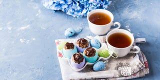 Süße Schale Ostern backt treets in den bunten Eierschalen auf Blau zusammen Stockbild