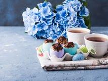 Süße Schale Ostern backt treets in den bunten Eierschalen auf Blau zusammen Stockfotografie