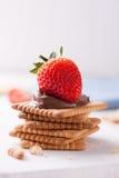 Süße schmelzende Nougatcreme der Schokolade auf Plätzchen mit Erdbeeren stockfotografie