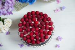 Süße Torte mit Schlagsahne und Himbeeren in Form von blac Lizenzfreies Stockfoto
