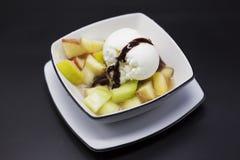 Süßer geschmackvoller Obstsalat mit einer Schaufel der Eiscreme und der Milchschokolade Lizenzfreie Stockbilder