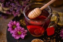 Süßer Honig auf Tasse Tee Stockfoto