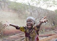 Süßer kleiner afrikanischer Junge unter dem Regen in Mali Africa lizenzfreie stockfotografie