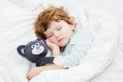 Süßer kleiner Junge, der im Bett schläft Lizenzfreie Stockfotos