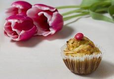 Süßer kleiner Kuchen mit einem Blumenstrauß von drei Tulpen auf einer Tabelle Lizenzfreie Stockbilder