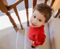 Süßer Kleinkindjunge, der hinunter die mit Teppich ausgelegte Treppe oben schaut mit a geht Stockfotografie
