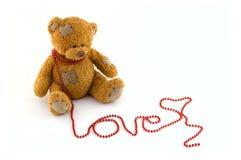 Süßer Teddybär mit einer Zeichenkette des Rotes bördelt arrang Lizenzfreie Stockbilder