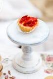 Süßer und köstlicher Kuchen mit Erdbeeren auf einem Stand Schäbige schicke Art Stockfoto