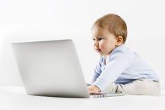 Süßes Baby, das mit Neugier Laptopschirm betrachtet. Stockfotos