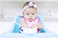 Süßes Baby, das mit Schüssel auf Stuhl isst Stockfotos