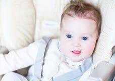 Süßes Baby in einem Hochstuhlwarteabendessen Stockfotos