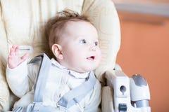 Süßes Baby in einem Hochstuhlwarteabendessen Stockbilder