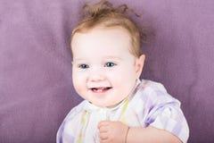 Süßes Baby in einem purpurroten Kleid auf purpurrotem Hintergrund Stockfotografie