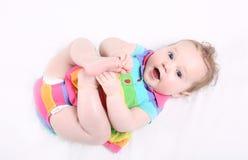 Süßes Baby im bunten gestreiften Kleid, das mit ihren Füßen spielt Stockfotografie