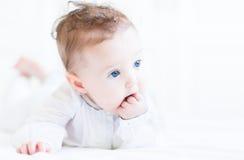 Süßes Baby mit den schönen blauen Augen, die auf ihren Fingern saugen Stockfoto