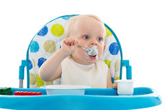 Süßes Baby mit Löffel isst den Jogurt. Lizenzfreies Stockfoto