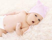 Süßes bequemes Baby im Hut gähnt, liegend auf dem Bett Lizenzfreie Stockbilder