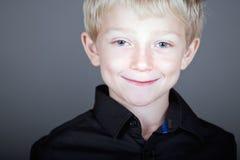 Süßes blondes behaartes Kind gegen grauen Hintergrund Lizenzfreie Stockfotografie