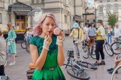 Süßes blondes Mädchen in einem alten Kleid mit Make-up, malende Lippen durch Lippenstift in der Menge des Festivals in Europa Lizenzfreie Stockbilder