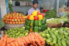 Süßes Capciam, Chili Red Green Yellow Sweet-Pfeffer im bangladeschischen Gemüseshop mit Shop-Wächter lizenzfreie stockfotos