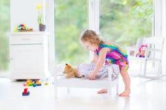 Süßes gelocktes Kleinkindmädchen, das mit ihrem Teddybären spielt Lizenzfreie Stockbilder