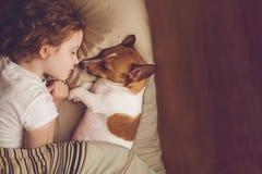 Süßes gelocktes Mädchen und Steckfassungsrussell-Hund schläft in der Nacht lizenzfreie stockfotografie