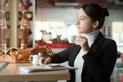 Süßes Hörnchen und ein Tasse Kaffee im Hintergrund Stockfotos