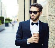 Süßes Hörnchen und ein Tasse Kaffee im Hintergrund Geschäftsmann in einem Anzug und in einem Glas Kaffee in einer Stadt, Geschäft Stockbild