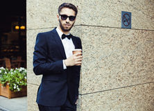 Süßes Hörnchen und ein Tasse Kaffee im Hintergrund Geschäftsmann in einem Anzug und in einem Glas Kaffee in einer Stadt, Geschäft Lizenzfreies Stockfoto