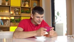 Süßes Hörnchen und ein Tasse Kaffee im Hintergrund Junger Mann, der Spiel am Handy spielt stock footage