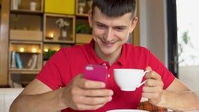 Süßes Hörnchen und ein Tasse Kaffee im Hintergrund Mann, der APP an seinem Handy verwendet stock video footage