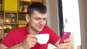 Süßes Hörnchen und ein Tasse Kaffee im Hintergrund Mann, der Mobiltelefon beim Trinken des Kaffees verwendet stock footage