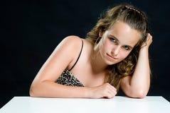 Süßes junges Mädchen, das auf weißer Tabelle sich lehnt Lizenzfreie Stockfotografie