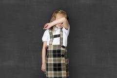 Süßes Juniorschulmädchen mit dem Schreien des blonden Haares traurig und schüchtern vor Schulklassetafel lizenzfreie stockbilder