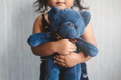 Süßes kleines asiatisches Mädchen, das ihren Lieblingsspielzeugteddybären umarmt stockfotografie