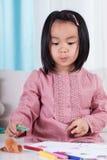 Süßes kleines asiatisches Mädchen mit Zeichenstiften Lizenzfreie Stockbilder