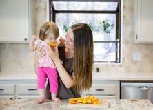 Süßes kleines Baby, das auf der Tabelle, eine Orange essend steht Lizenzfreie Stockfotografie