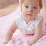 Süßes kleines Baby, das auf ihrem Bauch liegt. Stockbild