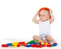Süßes kleines Baby mit Sturzhelm und Spielwaren. Lizenzfreies Stockfoto