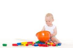 Süßes kleines Baby mit Sturzhelm und Spielwaren Stockbild