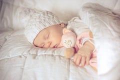 Süßes kleines Baby schläft mit einem Spielzeug Stockfotografie