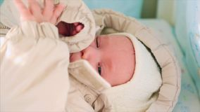 Süßes kleines Baby zu Hause gekleidet im knittede im sonnigen Schlafzimmer stock footage