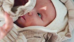 Süßes kleines Baby zu Hause gekleidet im knittede im sonnigen Schlafzimmer stock video footage