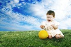 Süßes kleines Kind, das mit einem Ball auf dem Rasen spielt lizenzfreie stockfotos
